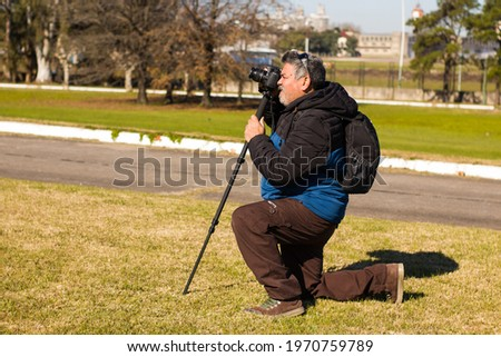 An adult man, crouching with a camera mounted on a monopod, in the park with green areas.