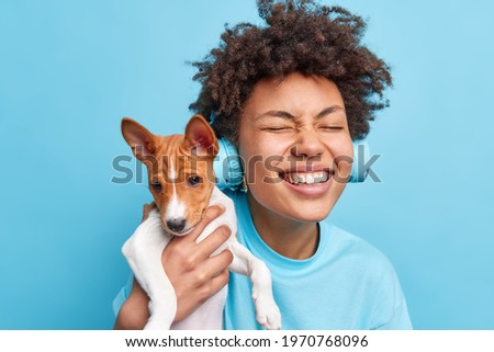 Happy curly haired teenage girl plays with pedigree dog enjoys company of favorite dog have walk together closes eyes wears stereo headphones listens music dressed casually isolated on blue background Royalty-Free Stock Photo #1970768096