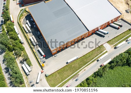 cargo trucks in industrial warehouse or logistic center waiting for loading goods. aerial photography with drone