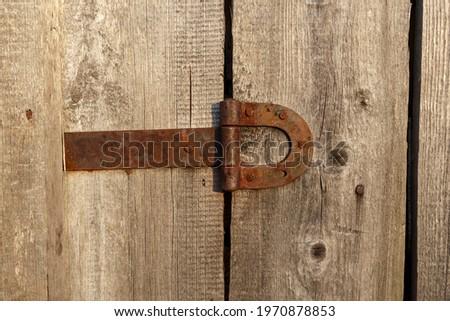 Old rusty metal door hinge. Door hinge on a wooden wall. Royalty-Free Stock Photo #1970878853