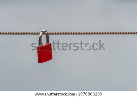 A red lock hanging on a wire rope symbolizing romance, proof of love, love forever and oath. Metallic red locks on wire string for happiness, Valentines day, faithfulness and lasting love. Love locks.