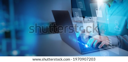 ERP, document management concept.Businessman working with laptop computer with icons on virtual screen and office blur background. Royalty-Free Stock Photo #1970907203