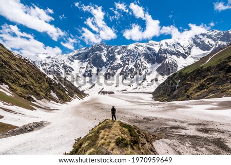 A lone hiker looks at the view of the Himalayas on the Beas Kund trek in northern India Royalty-Free Stock Photo #1970959649