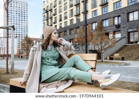 Young modern woman in coat and hat sits on a bench against the background of a city street