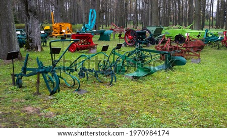 A set of old, restored agricultural machinery on the lawn in front of the museum. Picture taken on a cloudy day, soft light