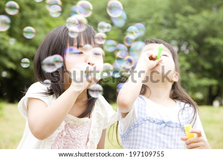 Two Girls Playing With Soap Bubbles #197109755