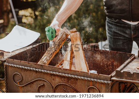 Man's hands setting fire at barbecue with firewoods by gas burner on the back yard. Picnic concept. Focus is at woods.