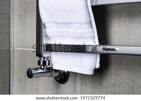 fragment of a chrome steel bathroom towel dryer on the gray anthracite tile wall Royalty-Free Stock Photo #1971329774