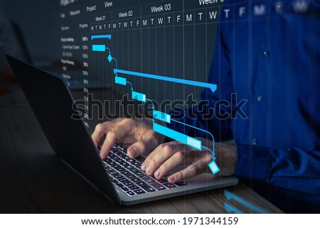 Project manager working on Gantt chart to update the schedule, tasks and milestones progress for the team. Management diagram on computer screen with person coordinating teamwork. Royalty-Free Stock Photo #1971344159