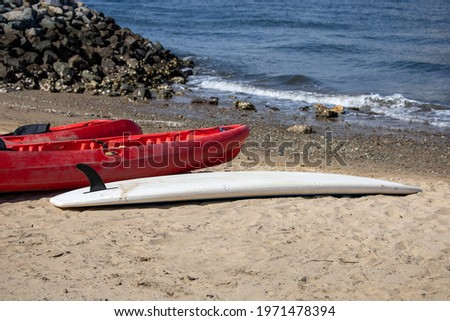 A paddle board and view of two kayaks by the seashore.