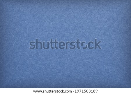The surface of blue cardboard. Paper texture with cellulose fibers. Elegant tinted background with vignetting. Glamorous generic gray paperboard wallpaper. Beautiful textured backdrop. Top-down. Macro