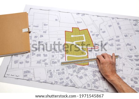 Town planning and land use planning - hand holding a measuring ruler in front of a zoning of plots, on a cadastral plan placed on a desk Royalty-Free Stock Photo #1971545867
