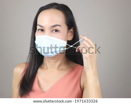 Close up image of Asian woman wearing medical or surgical face mask which improved to be fit, showing the knot and looking at camera. Royalty-Free Stock Photo #1971633326