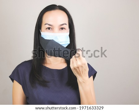 Portrait of Asian woman wearing  double face masks  or two face masks for better protection  from coronavirus or covid-19 outbreak - concept of safety, healthcare, medical and hygiene.