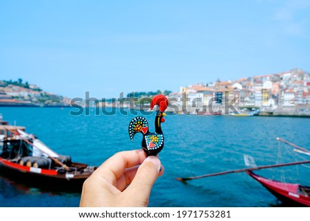 closeup of a young caucasian man holding a traditional Rooster of Barcelos, the emblem of Portugal, in Porto, at the Douro River with the Ribeira district on the right Royalty-Free Stock Photo #1971753281