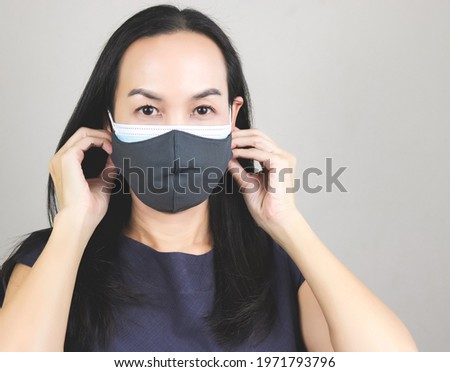 Close up image of Asian woman wearing  double face masks  or two face masks for better protection  from coronavirus or covid-19 outbreak - concept of safety, healthcare, medical and hygiene. Royalty-Free Stock Photo #1971793796