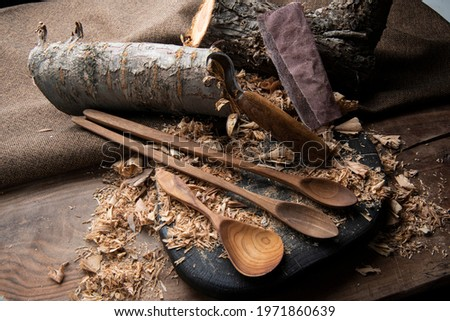 hand carved spoon with raw woods and carving tools Royalty-Free Stock Photo #1971860639