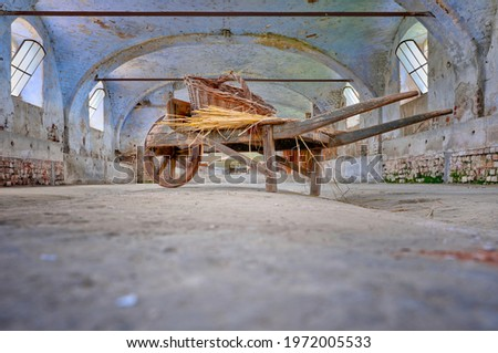 A small wooden handcart, with a wicker basket on top, in an old abandoned barn Royalty-Free Stock Photo #1972005533