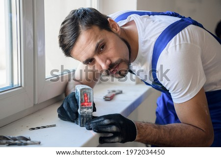 The handyman uses the level on the windowsill