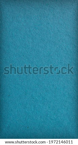The surface of blue-green cardboard. Bright mobile phone wallpaper. Dark vertical background. Rough natural paper texture with cellulose fibers. Coloured paperboard with edge vignetting. Macro