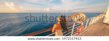 Happy cruise woman relaxing on deck feeling free watching sunset from ship on Caribbean travel vacation. Panoramic banner of sea and boat. Royalty-Free Stock Photo #1972157453