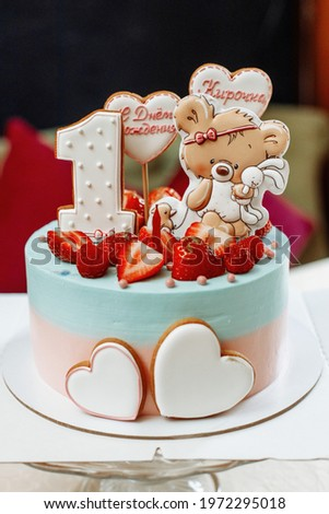 A beautiful birthday cake for a children's birthday. Gift for a girl for 1 year. Decorations on the cake with strawberries and cartoon characters, hearts. The inscription - Happy Birthday Kirochka