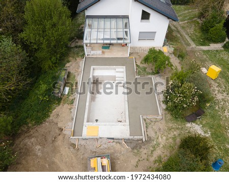 aerial drone flight pic of Swimming pool construction site from above in a garden in austria