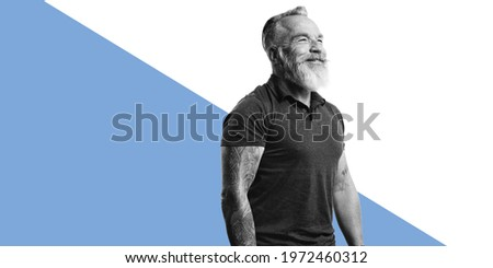 Happy senior man with tattoo on arms standing against dual tone background. Portrait of old muscular male with white beard looking away. Royalty-Free Stock Photo #1972460312