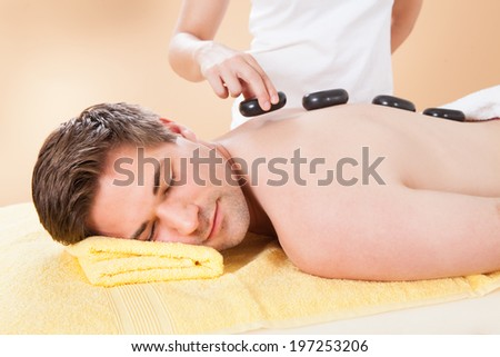 Relaxed young man receiving hot stone therapy in spa #197253206