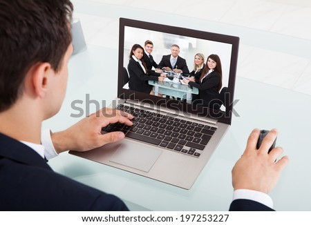 Cropped image of young businessman video conferencing on laptop at desk in office #197253227