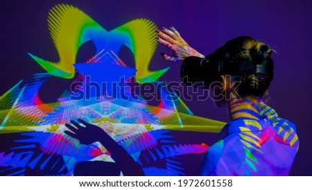Woman using VR headset and waving hands in front of large wall display with augmented reality mirror effect at modern futuristic immersive exhibition or museum. AR, future, art, technology concept Royalty-Free Stock Photo #1972601558