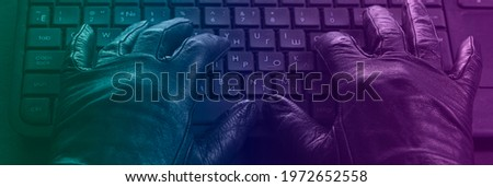 Cybercriminal, hands in gloves on laptop keyboard, photo toned in neon light. Royalty-Free Stock Photo #1972652558