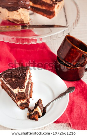 Dark chocolate cake with Coffee slice with chocolate buttercream frosting on a white plate.Selective focus. Royalty-Free Stock Photo #1972661216