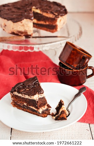 Dark chocolate cake with Coffee slice with chocolate buttercream frosting on a white plate.Selective focus. Royalty-Free Stock Photo #1972661222