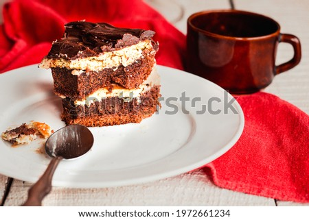 Slice of three chocolate cake on a plate. Delicious tasty homemade cake on table. White wooden background. Young woman eating dessert process. Royalty-Free Stock Photo #1972661234