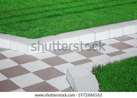 Path from Ceramic Tiles and Boarders Between Walkway and Backyard Lawn. Ceramic Tile Walkway. Garden Pathway from Black and White Tiles. Royalty-Free Stock Photo #1972686563