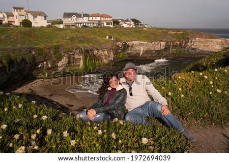 A friendly couple comfortably sitting on a cliff against a beautiful shoreline coast of Santa Cruz, California, USA