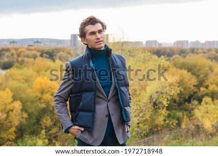 Tall handsome man walking outdoor in yellow autumn forest on the hill Royalty-Free Stock Photo #1972718948