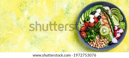 Grilled chicken meat and fresh vegetable salad on yellow background. Healthy and detox food concept. Ketogenic diet. Buddha bowl dish, Long banner format, top view,