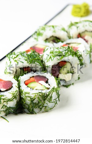 Sushi rolls with tuna, cucumber and cream-cheese in chopped dill. Served on a white plate over white background. Traditional Japanese cuisine concept, sushi recipe.