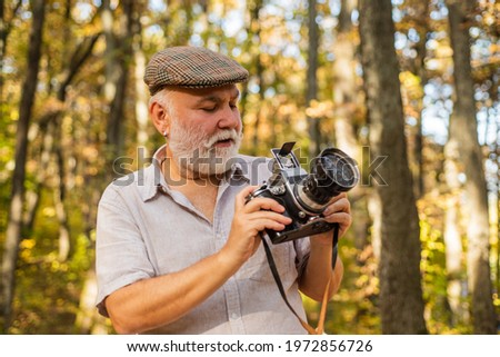 Photo session using natural light. Senior man take photo on autumn day. Old photographer hold photo camera. Landscape and nature photo shooting. Hobby or professional activity