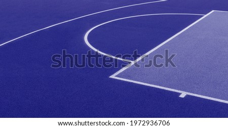 Abstract, blue background of newly made outdoor basketball court. Visible asphalt texture, freshly painted lines. Blue color filter