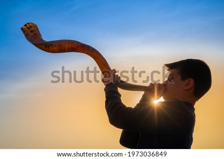 Teen boy blowing Shofar - ram's horn traditionally used for Jewish religious purposes, including the Feast of trumpets, Yom Kippur and Rosh Hashanah; beautiful sunset sky with sunburst in bachground Royalty-Free Stock Photo #1973036849