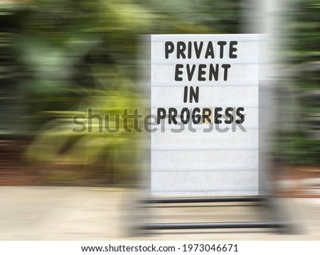 Sign in ornamental garden - Private Event in Progress - surrounded by motion blur of sidewalk, display stand, and greenery, for concepts of restriction and time, perception, alternate reality