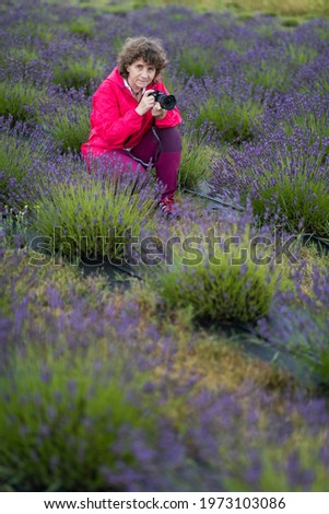Matured woman is taking a picture in a lavender field in Poland.
