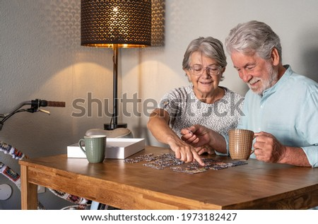 Smiling senior couple doing a jigsaw puzzle at home on wooden table. Vintage bicycle in the corner Royalty-Free Stock Photo #1973182427
