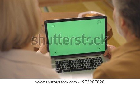 Elderly couple is looking at the computer screen with green tracking markers during the epidemic. Shoot from the shoulder. Creative people can put any image they want on the green screen.