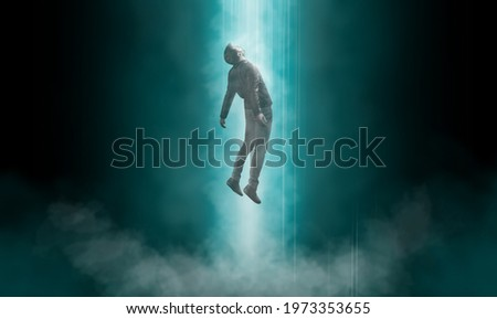 Man being abducted by UFO - alien abduction concept Royalty-Free Stock Photo #1973353655