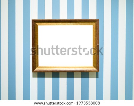 gold painted wooden picture frame with cutout canvas on blue striped wall Royalty-Free Stock Photo #1973538008