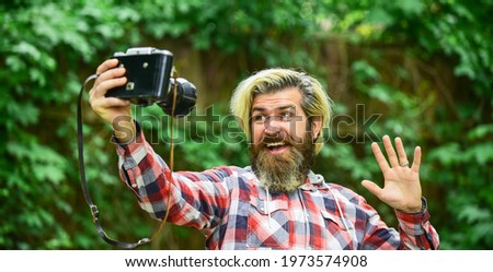 photography in modern life. travel tips. professional photographer use vintage camera. selfie time. bearded man hipster take photo. photo shooting outdoor. brutal man traveler with retro camera